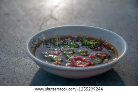Hot and spicy green and red chilli in soy sauce serve in small plate on old table at local restaurant in Penang Malaysia #1255299244
