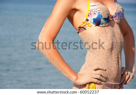 Hot and wet. Close-up of sandy woman perfect body
