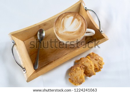Hot art cappuccino Coffee in a cup on wooden table and Coffee shop white background.