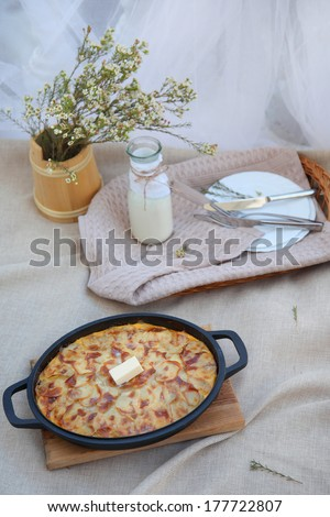 Hot baked meal with a slice of melted butter in the center. Flowers on the table, a tray of dishes and appliances, and flowers.