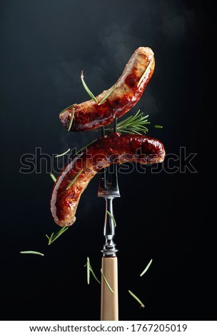 Hot Bavarian sausages with rosemary.  Sausages  on a fork sprinkled with rosemary. Stock photo ©