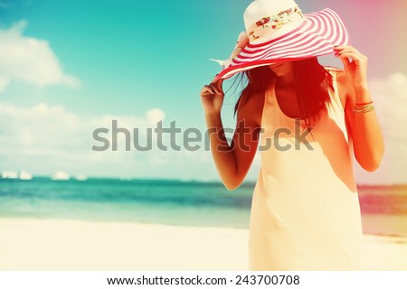 Hot beautiful woman in colorful sunhat and dress walking near beach ocean on hot summer day on white sand #243700708