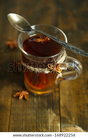 Hot beverage in glass cup with fruits and spices, on wooden background - stock photo