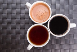 Hot beverages of tea, chocolate and black coffee on a woven place mat