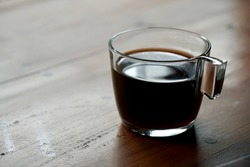 hot black coffee in transparent cup placed on wooden table in morning light with copy space. toned color photo.