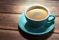 Hot black coffee or Americano in blue ceramic cup on wooden table background.