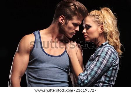 Hot blonde woman holding her hands on her boyfriend shoulder, both looking away. On studio background.
