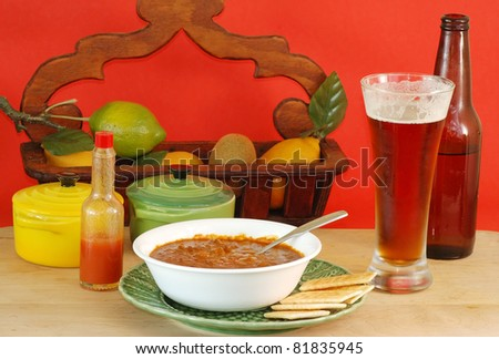 Hot bowl of chili and cold bottle of beer at local pub or bar in colorful surroundings.