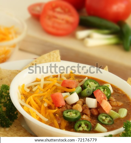 Hot bowl of Chili with green onions, tomatoes, jalapenos and cheese