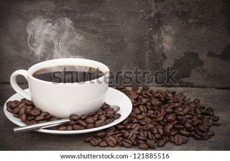 Hot breakfast coffee cup and saucer surrounded by coffee beans on rustic background