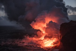 Hot bright lava streams flowing into the ocean making big clouds of steam against sunset sky on background