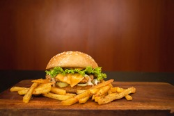 Hot Burgers and french fries on wooden background, with crispy chicken or grilled meat beef   Cheese Ham with Onions and Bacon Big single cheeseburger, with fried potatoes chips   mayonnaise sauce.