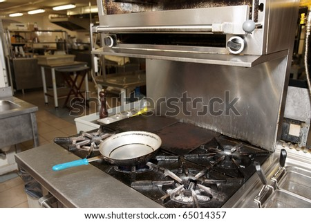 Hot busy kitchen with gas range in foreground