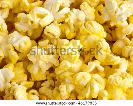 Hot buttered popcorn closeup, bright white and yellow background.