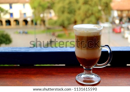 Hot cappuccino coffee in a transparent cup served at the terrace with blurred old town square of Cusco, Peru in background #1131615590