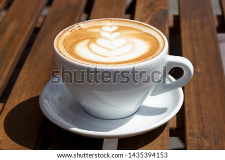 Hot cappuccino with froth and pattern on wooden background, a side view