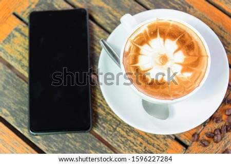 hot cappuccino with nice milk pattern and smart phone on work space table in office