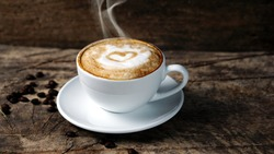Hot cappuccino with streamed milk. Pour the hot milk made a heart. A cup of strong coffee put on the wood table with shiny dark roasted Italian coffee beans. Aroma espresso and flavor beverage.
