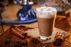 Hot chai latte with spices like cinnamon, cardamon, cloves, star anise as a sweet warm winter dessert drink