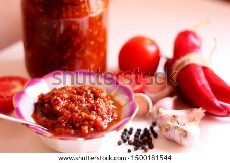Hot chilli pepper tomato sauce paste with garlic in bowl closeup. Adjika, hot harissa sauce - spicy hot paste of chilli pepper, tomato on table. Tomato hot ketchup sauce with chilli pepper paste food