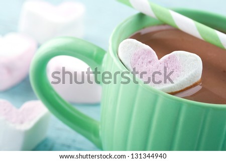 Hot chocolate and a heart shaped marshmallow in a green cup