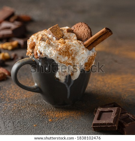 Hot chocolate cocoa cup with whipped cream decorated with cinnamon, chocolate slices and cookies  on concrete background. Tasty beverage for cold days . ストックフォト ©