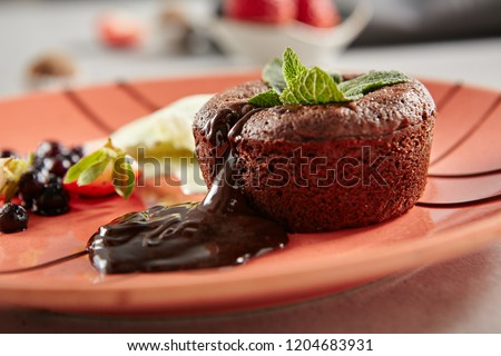 Hot Chocolate Fondant with Mint Leaves and Berries on Terracotta Plate Close Up. Fresh Brownie Dessert with Melted Dark Cocoa Mousse. Small Chocolate Cake with Crunchy Rind and Mellow Filling Photo stock ©