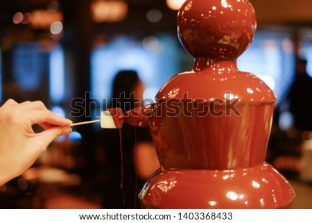 hot chocolate fondue fountain with a slice of fruits on a fork being dipped  #1403368433