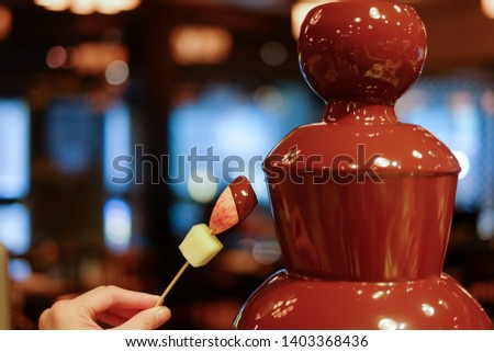 hot chocolate fondue fountain with a slice of fruits on a fork being dipped  #1403368436