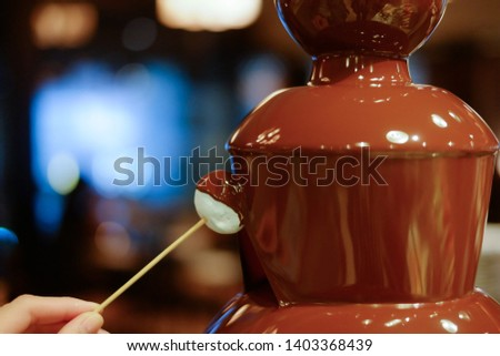 hot chocolate fondue fountain with a slice of fruits on a fork being dipped  #1403368439