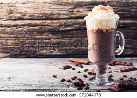 Shutterstock Hot chocolate garnished with whipped cream and cocoa powder .