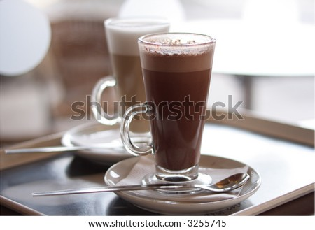 Hot chocolate in a tall class with Cafe Latte on background - stock photo