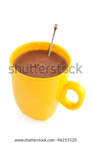 Hot chocolate in a yellow mug with silver spoon - stock photo