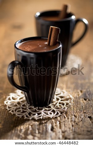 hot chocolate in black mugs with cinnamon stick, on old wooden table backdrop