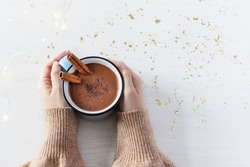 Hot chocolate with cinnamon spice in enamel mug in female hands on white wooden background top view. Hot cozy drink for autumn or winter season.