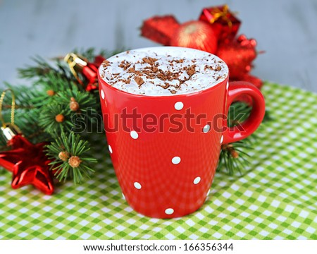 Hot chocolate with cream in color mug, on napkin, on Christmas decorations background