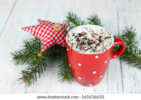 Hot chocolate with cream in color mug, on table, on Christmas decorations background
