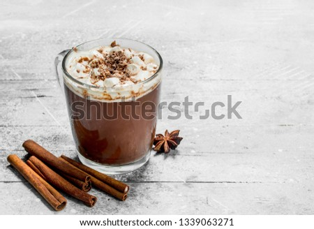 Hot chocolate with marshmallows and cinnamon. On a rustic background. #1339063271