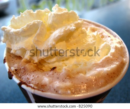 Hot chocolate with whipped cream in a paper cup, closeup