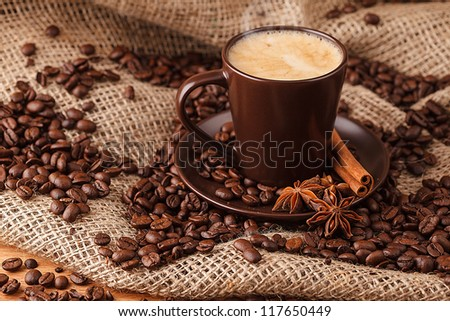 Hot Christmas cup of coffee with coffee beans on background.