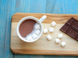 hot coco hot chocolate in mug with marshmallows and chocolate bar on the side of the mug on a wooden board on a green wooden background/hot chocolate/mug of hot chocolate