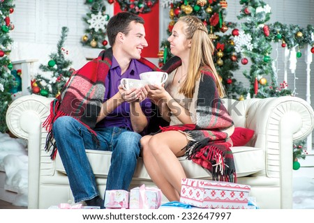 Hot cocoa Christmas. A loving couple holding cups and drinks at Christmas. Young couple in love man and pretty girl wearing sweater and scarf at home