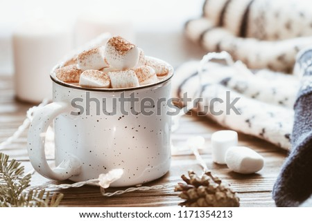 Hot cocoa with marshmallow in a white ceramic mug surrounded by winter things on a wooden table. The concept of cosy holidays and New Year.