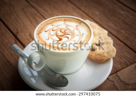Hot coffee and cookie on saucer with wooden background
