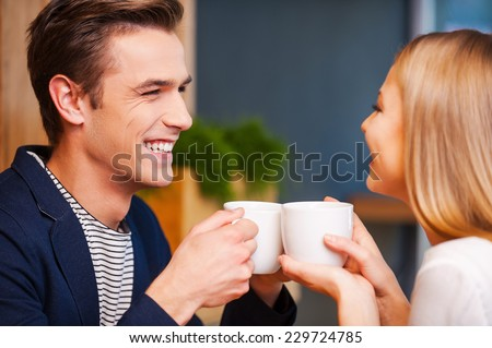 Hot coffee and hot love. Beautiful young couple looking at each other and smiling while enjoying coffee in cafe together
