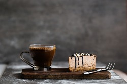 Hot coffee and  slice of raw chocolate mousse cake with cashew, hazelnuts and dark chocolate glaze topping on a wooden and grey background. Vegan sugar gluten free dessert. Copy space, horizontal