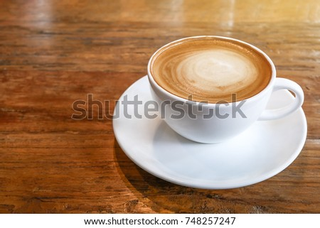 Hot coffee cappuccino cup with spiral milk foam on wood table background.