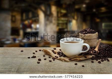 Hot Coffee cup and coffee beans roating on the wooden table and the coffee shop background with copy space #577416223
