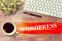 Hot coffee cup and keyboard with wordpress inscription on table