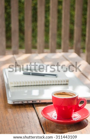 Hot coffee cup on wooden work station, stock photo